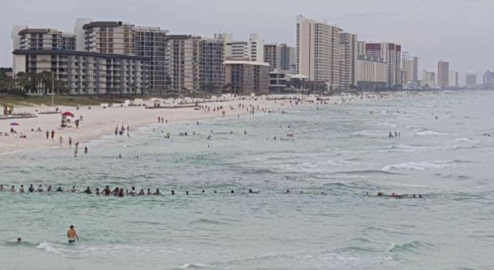 Beachgoers form human chain to rescue family in water