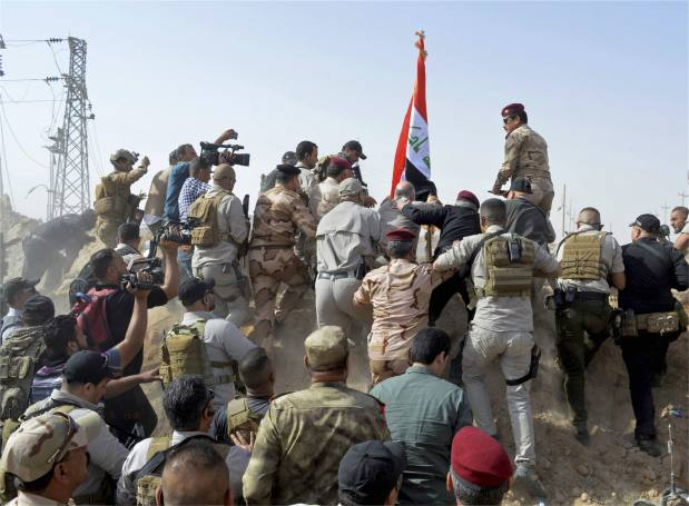 Iraqi PM raises flag at border crossing taken from IS