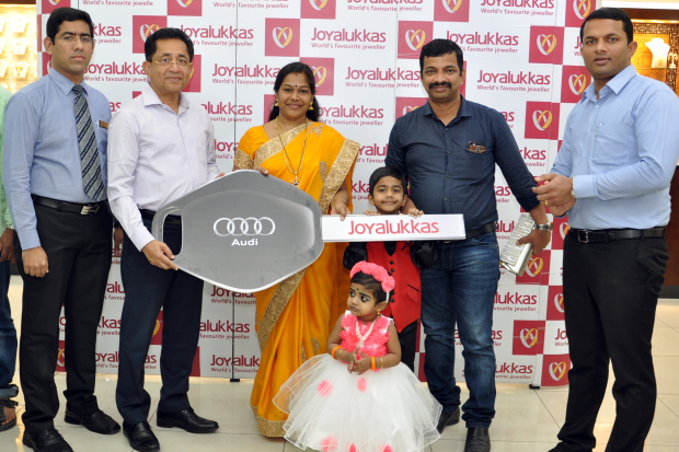 <p><em>Mrs Prasad receives the key to the car from Joyalukkas chairman and managing director Joy Alukkas in the presence of her husband and children, and officials</em></p>