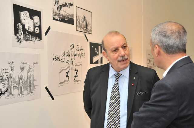 <p>Palestinian Ambassador Taha Mohammed Abdul Qader, left, discusses some of the cartoons on display with another guest.</p>