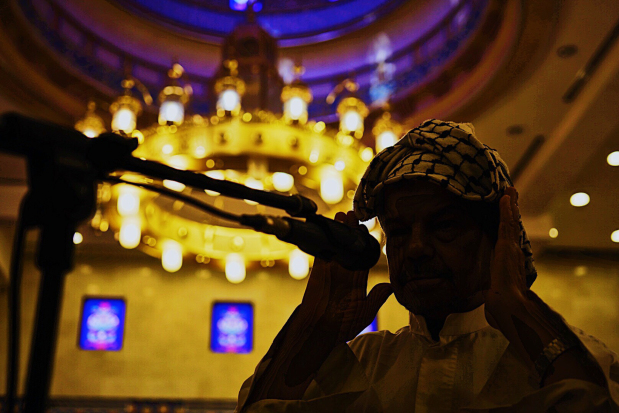 <p>A prayer caller, or muezzin, performs the adhan, the call to prayer, at a Bahrain mosque. The ritual is performed five times every day, summoning Muslims to worship. The role of muezzin is important as members of the community rely on the adhan to keep an accurate prayer schedule, particularly during Ramadan - since at sunset it is a sign for them to break their fast. The muezzin faces the Qiblah, the direction of the Kaaba in Mecca, while performing the adhan. Historically, they climbed to the top of minarets and recited the call so as to be heard by those nearby, but these days the use of microphones and loudspeakers mean that is not necessary. (Picture: Ahmed Rajab)</p>