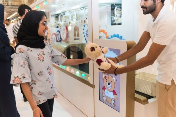 <p><em>A young visitor receives a teddy bear as part of the drive.</em></p>