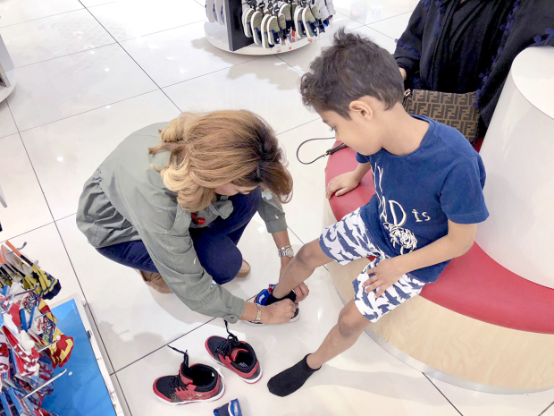 <p>A child trying out a shoe with the help of an organiser.</p>