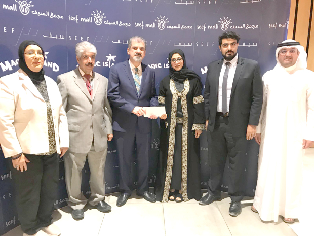 <p><em>Seef Properties chief executive Isa Najeebi, third from left, presents a cheque to Smile Initiative financial secretary and psychological support head Safaa Al Nasser, third from right , in the presence of other officials</em></p>