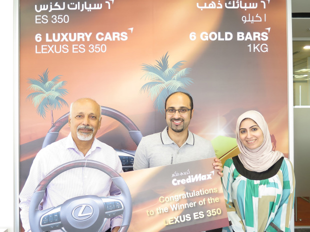 <p><em>Mr Esbai receives his prize from customer service officials Jassim Mohammed and Aysha Rafea.</em></p>