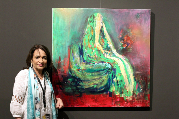 Fareeda Khalaf displaying one of her paintings