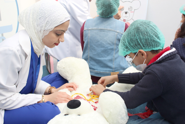 """<p><em>One of the children """"inspecting"""" a teddy bear</em></p> <p>Nearly 1,100 children took part in the Second Teddy Bear Hospital awareness campaign held at The Avenues mall.</p> <div>The two-day initiative, organised by the Arabian Gulf University (AGU), was created to simulate a real hospital and aimed at removing children's fear of hospitals and doctors.</div> <div></div> <div>Children were allowed to play the role of doctors and examine teddy bears, with the help from 120 AGU medical students.</div> <p><em><br /></em></p>"""
