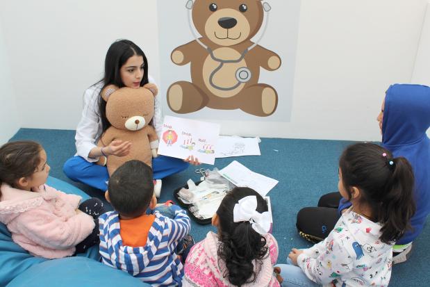 A medical student addresses children