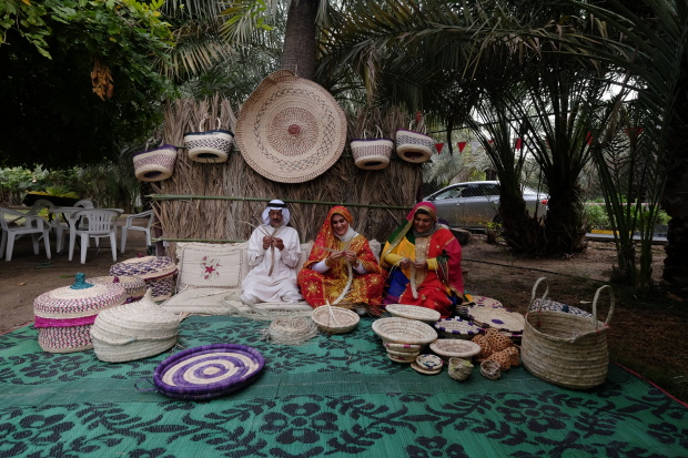 <p>Basket weavers dressed in traditional attire display their skills.</p>