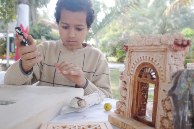 <p>A young boy uses a traditional tool to carve some gypsum.</p>