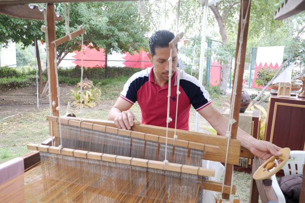 <p>A textile weaver shows his craft.</p>