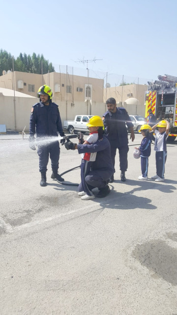 <p>A fireman shows a student how to fight a blaze.</p>