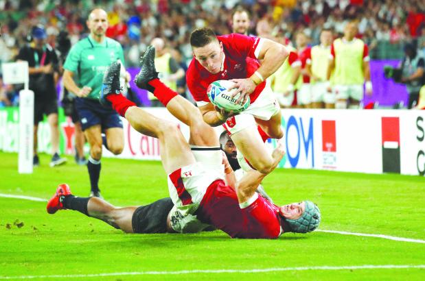 Adams powers Wales into quarters