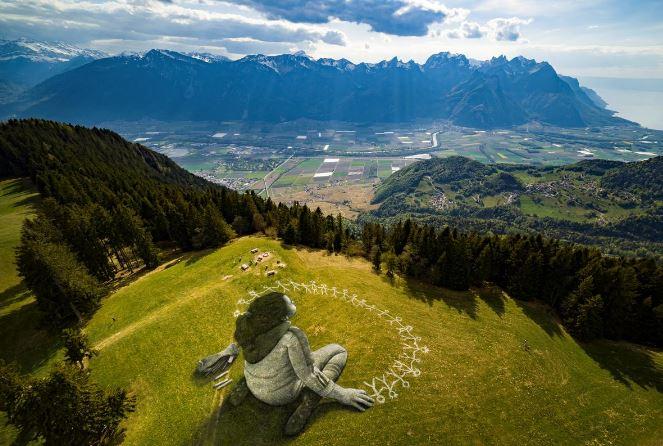 Massive virus-themed grass graffiti unveiled in Swiss Alps