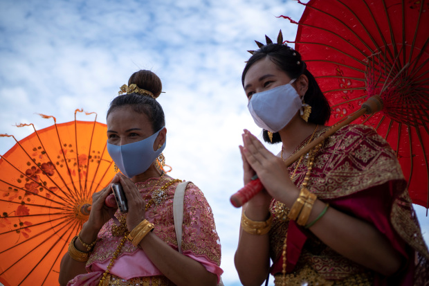 Thais return to temples in traditional garb - and masks