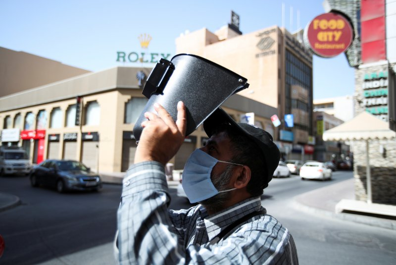 """<p><span>A man wearing a protective face mask uses a welding helmet as a protection to watch the annular solar eclipse, in Manama,</span><span data-qa-component=""""highlight-text"""" class=""""highlight"""">&nbsp;Bahrain</span><span>, June 21, 2020.</span></p>"""