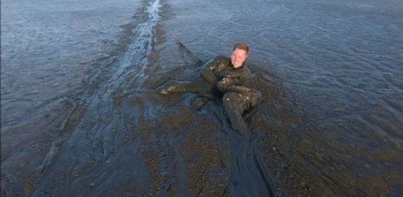 VIDEO: Drone films Photographer's Incredible crawl through mud to rescue an Eagle
